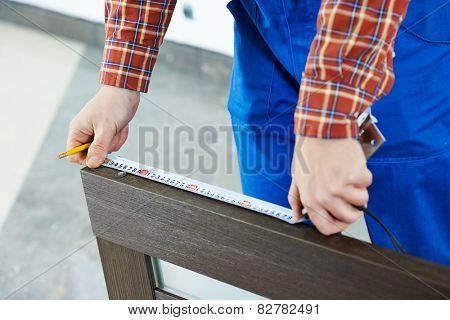 Close-up carpenter hands with measure tape during process of wood door installation