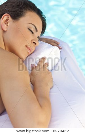 Beautiful Young Woman Relaxing By Pool At Health Spa