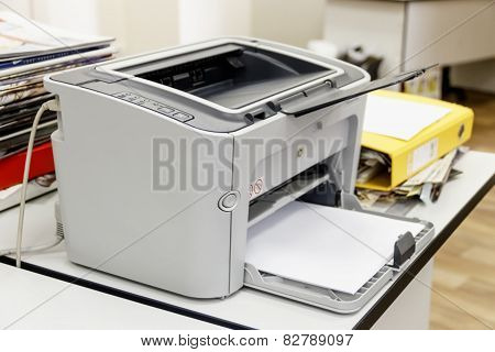 Printer In The Office Among Papers And Folders