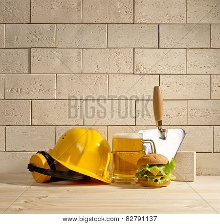 Beer And Burger With The Helmet And Trowel Against A Brick Wall