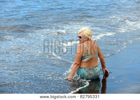 Aged Woman On The Wet Black Sand Of Arena Beach.