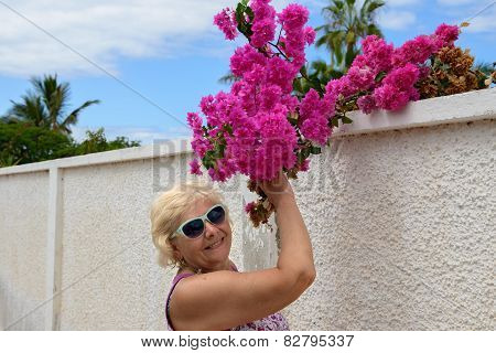 Portrait Of Aged Woman With Red Bougainvillea Leaves.