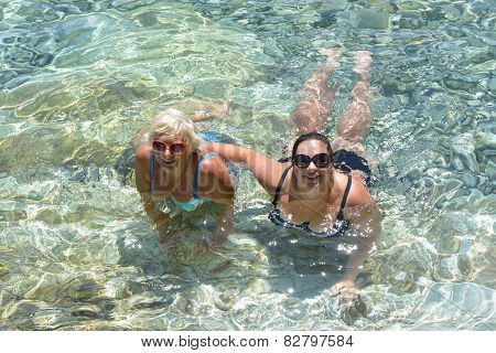 Women Lie In Clear Transparent Sea Water.