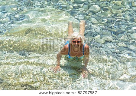 Woman Lies In Clear Transparent Sea Water.