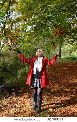Girl throwing leaves in autumnal woods