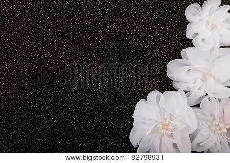 White fabric flowers on black background with sequins