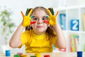 image of finger-painting  - cute child girl have fun painting her hands - JPG