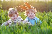 foto of bunny ears  - Two little boys with Easter bunny ears playing in green grass on Easter holiday - JPG