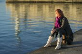 pic of peaceful  - Young woman daydreaming and enjoying the peaceful sunset at the harbour - JPG