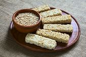 image of quinoa  - Popped quinoa seeds in bowl with quinoa cereal bars one with honey the other mixed with amaranth on wooden plate photographed with natural light  - JPG