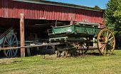 picture of wagon wheel  - Green old wooden wagon with it front wheels off - JPG