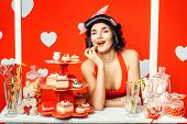 picture of porter  - PinUp Porter girl smiling and finger wipes corner of his mouth she stands in a booth with cakes and sweets - JPG