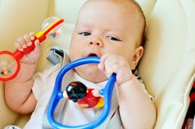 picture of teething baby  - baby laying in bouncer chair with toys - JPG