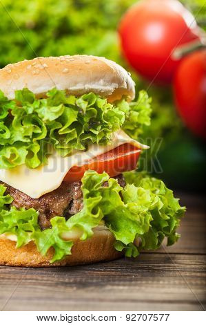 Cheeseburger With Lettuce, Onions And Tomato In A Sesame Bun