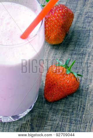 Strawberry milk shake with strawberries on wooden background soft focus on strawberry