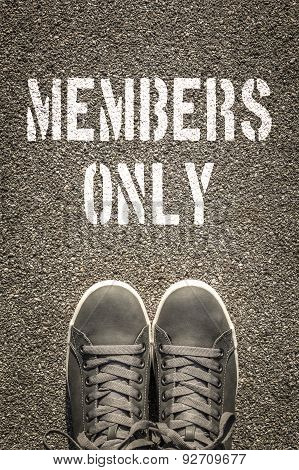 Members Only Stencil Print On The Asphalt Road