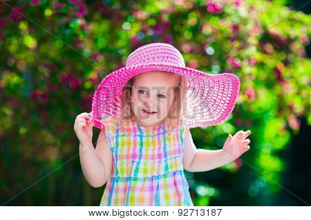 Little Girl In A Hat In Blooming Summer Garden