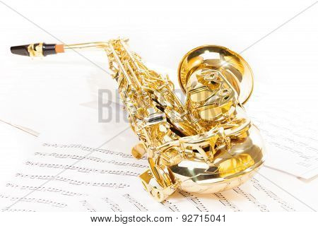 Alto saxophone laying on the musical notes