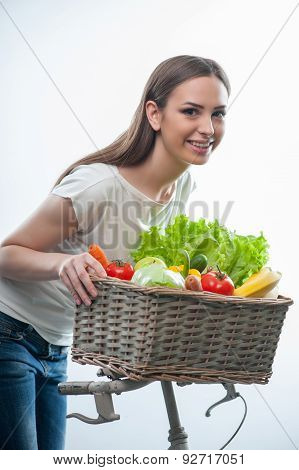 Pretty woman is standing with vegetarian food
