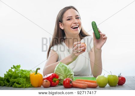 Pretty woman is sitting with fruits and vegetables