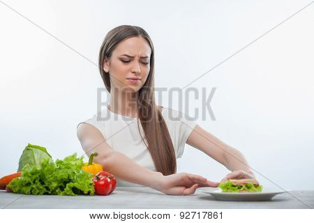 Cheerful young girl is choosing between healthy and harmful food