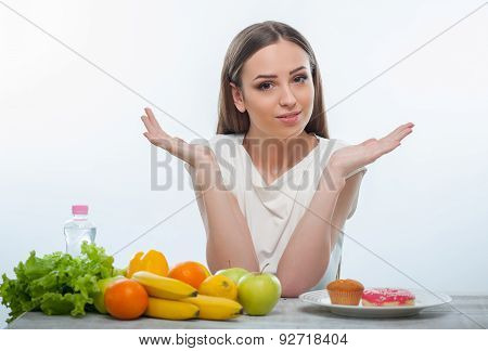 Beautiful young girl is choosing between healthy and unhealthy food
