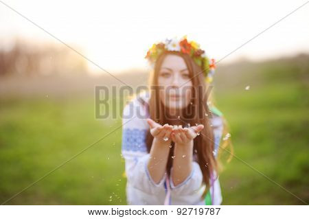 Girl In A Flower Wreath On His Head Blows Away The Fluff From His Hands