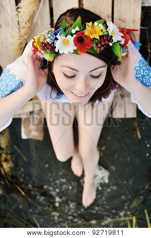 Girl In A Flower Wreath On His Head Sitting On The Bridge And Wets Feet In The River