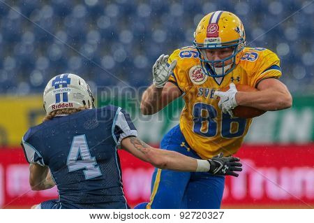 ST. POELTEN, AUSTRIA - JUNE 1, 2014: WR Johan Stal (#86 Sweden) is tackled by DB Pekka Rantala (#4 Finland).