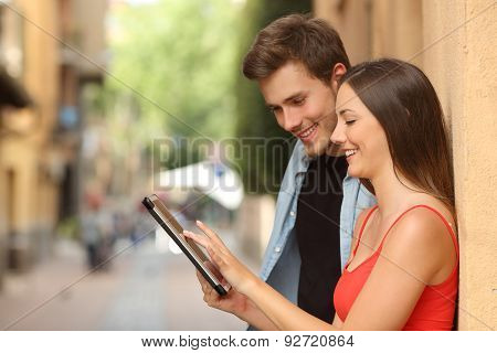 Couple Browsing A Tablet In The Street