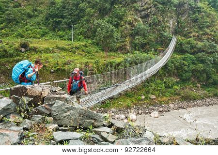 Tourists Crossing The River On A Suspension Bridge