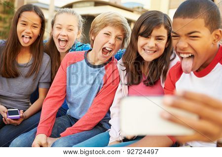 Group Of Children Sitting On Bench In Mall Taking Selfie