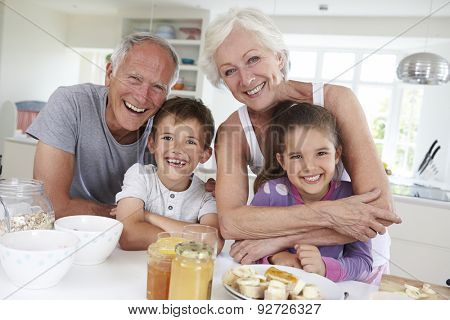 Grandparents With Grandchildren Eating Breakfast In Kitchen
