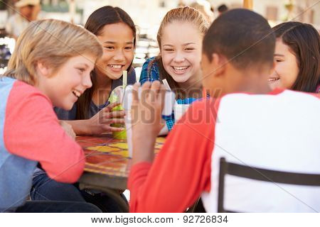 Group Of Children In Caf\x81_ Looking At Text On Mobile Phone