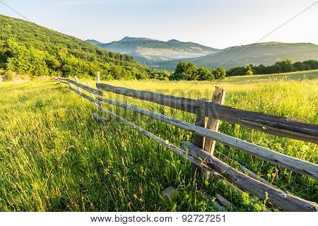 Fence On Hillside Meadow In Mountain