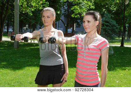 Two Sport Woman Doing Exercises With Lightweight Dumbbells