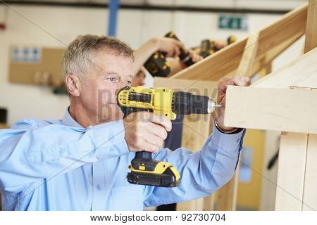 Mature Student Using Drill In Carpentry Class