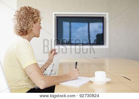 Senior Businesswoman Having Video Conference In Boardroom