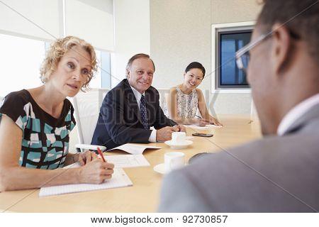 Four Businesspeople Having Meeting In Boardroom