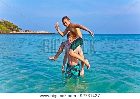 Brothers Are Playing Together In A Beautiful Sea With Crystal Clear Water And Blue Sky