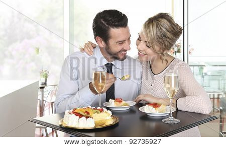Happy Couple At The Bar With Champagne And Fruit Cake, Love Concept