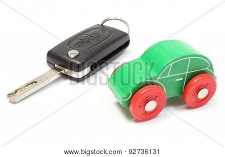 Old Green Toy Car And Vehicle Key On White Background