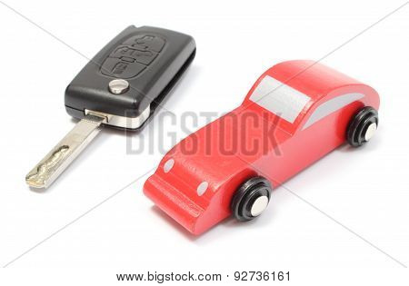 Old Red Toy Car And Vehicle Key On White Background
