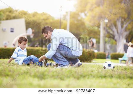 Father Looking After Son Injured Playing Football