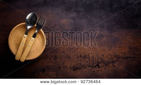 Wooden bowl ,fork and spoon on vintage background