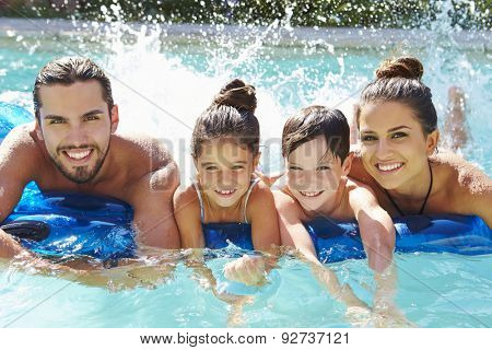 Portrait Of Family On Airbed In Swimming Pool