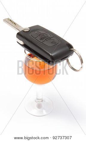 Car Key Lying On Glass Of Wine. White Background
