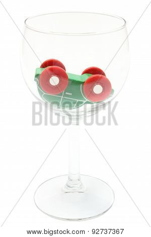 Overturned Car Model In Glass Of Wine. White Background