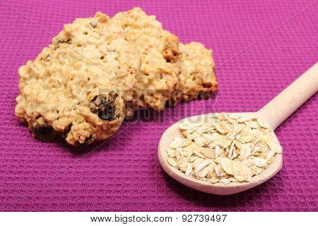 Oatmeal Cookies And Flakes On Wooden Spoon. Purple Background