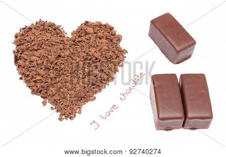 Heart Shaped Grated Chocolate And Three Candies On White Background